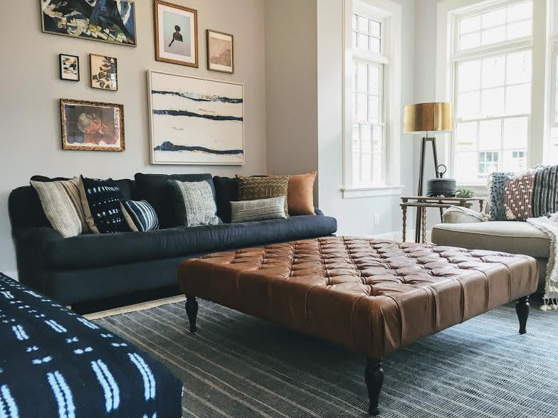 The foundation is timeless and classic with a navy, rolled-arm sofa, an oatmeal linen armchair, and an oversized leather ottoman.
