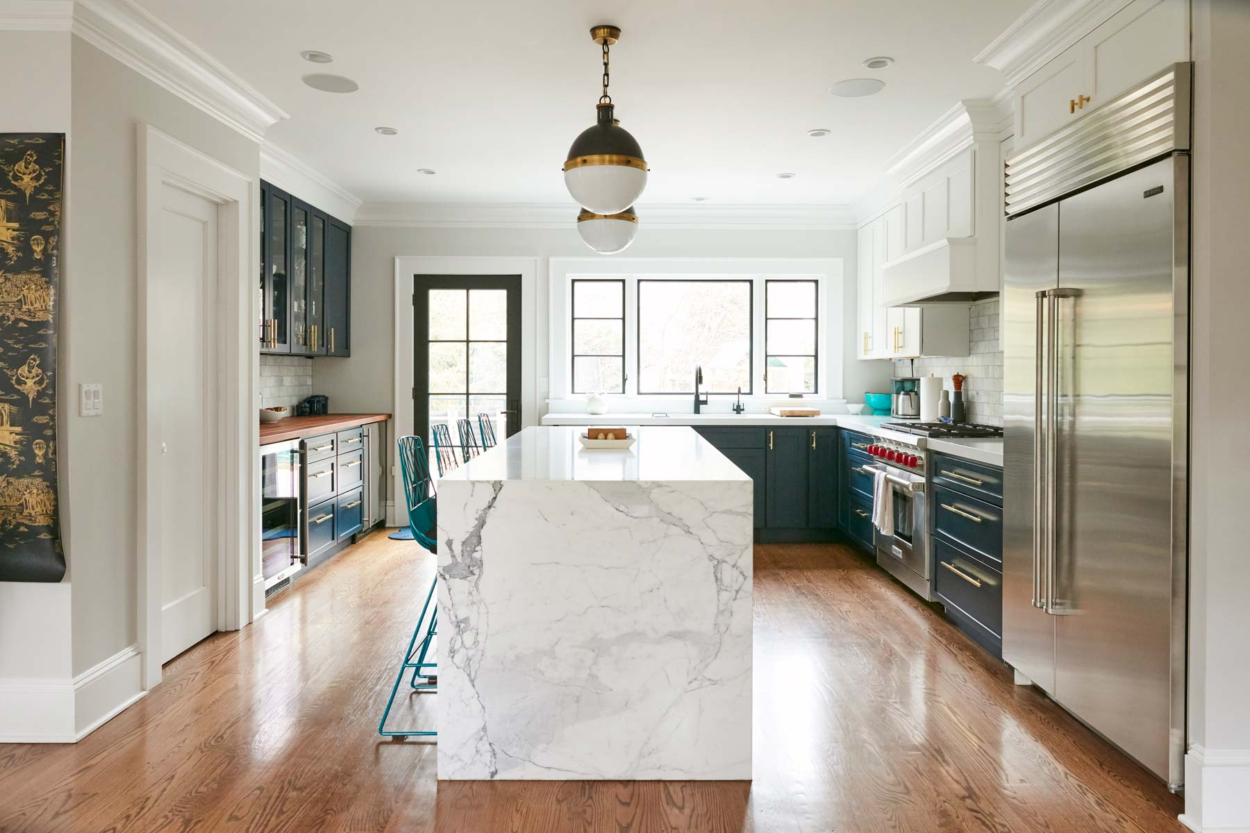 Kitchen cabinets in rich navy contrasted with a beautifully veined slab of marble. SNEAK PEEK! The Goldstein home is Alexis' ever-evolving art project. Check out the wallpaper sample on the left. It was designed by Mike D. Yes, that Mike D.
