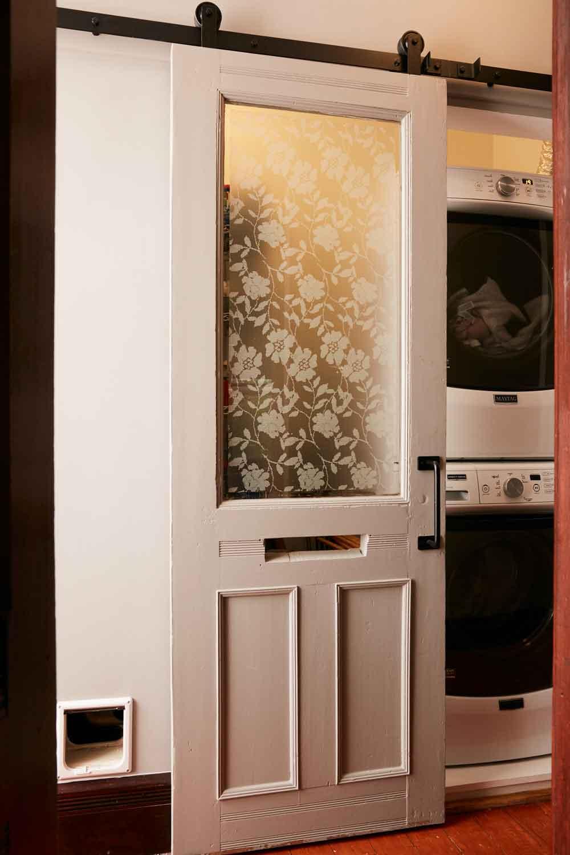 Jess Davis, owner of Nest Studio, original front doors used in laundry room as sliding barn doors DIY floor project in her South Orange NJ Victorian